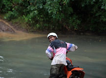 Crossing river. Man riding two wheel cross country vehicle Royalty Free Stock Images