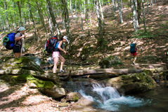 Crossing a river. Hikers cross a river with small waterfall Royalty Free Stock Image