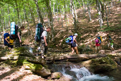 Crossing a river. Hikers cross a river with small waterfall Royalty Free Stock Photos