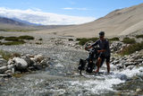 Crossing the river in Tibet. Cyclist crossing the river during journey in the remote part of Tibetan plateau, Tibet royalty free stock image