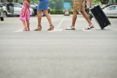 Crossing road. Cropped image of family with suitcase crossing the road Royalty Free Stock Photos