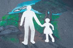 Crossing the road pavement art. Reminding parents to hold hands with their children when crossing the road Royalty Free Stock Photo