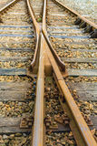 Crossing rusty rails from close. Closeup of intersecting railway lines of rust-colored rails supported on timber sleepers laid on crushed stone ballast Royalty Free Stock Images