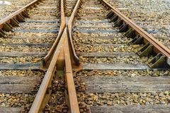 Crossing rusty rails from close. Closeup of intersecting railway lines of rust-colored rails supported on timber sleepers laid on crushed stone ballast Royalty Free Stock Photography
