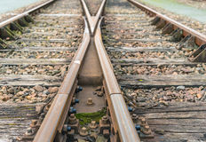 Crossing rusty rails from close. Closeup of intersecting railway lines of rust-colored rails supported on timber sleepers laid on crushed stone ballast Stock Photo
