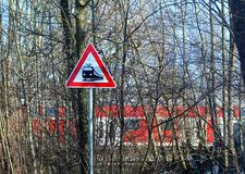 Crossing sign with train traveling, view from a rural road Royalty Free Stock Photography