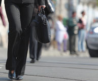 Crossing the street. Image of a businesswoman's lower body. She is carrying a computer bag while crossing the street in a city Stock Images