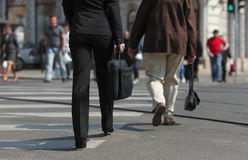 Crossing the street. Image of a businesswoman's lower body. She is carrying a computer bag while crossing the street in a city Royalty Free Stock Photos
