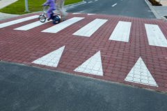 Crossing a street. Father with  a small girl on a bike crossing a street (motion blurred image Royalty Free Stock Photography