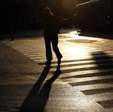 Crossing the street. Silhouette of woman crossing the street royalty free stock image