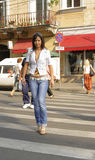 Crossing the street. Young woman crossing the street in an old city Royalty Free Stock Image