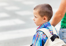 Crossing the Street. A cute little boy and his mother waiting to cross the street on their way to school Stock Photo