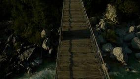 Crossing a suspension bridge stock video