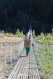 Crossing a Suspension Bridge. Trekking around the mountains of the Everest Foothills Sagamatha National park Nepal Stock Photo