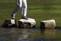 Crossing three stepping stones in a river. Landscape stock photos