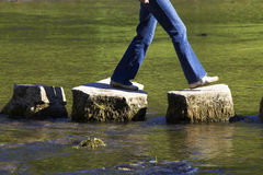 Crossing three stepping stones in a river. Female stock images