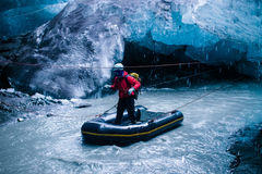 Crossing underground river in Iceland. Person crossing underground river in a rubber boat inside the blue ice cave under the glacier in Iceland Stock Photography