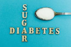 Crossing the words `sugar` and `diabetes`, a spoon with sugar on a blue background, concept royalty free stock image