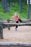 crossingflickan hoppar över little som är trä Arkivbild