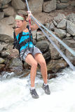 Crossings. A girl crosses a raging river via a tyrolean traverse Stock Photo