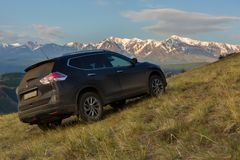Crossover Nissan X-TRAIL on the hillside in Kurai steppe against the backdrop of the North Chuy ridge at dawn. Altai Krai, Russia - July 15, 2015: Crossover Stock Image