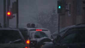 Crossroad of city with winter snow blizzard. driving Cars, walking people, red and green traffic lights stock video