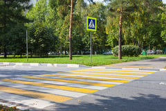Crossroad with yellow and white stripes and road sign Stock Photography