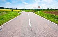 Crossroads. Asphalt Road between Fields of Lucerne in Germany Royalty Free Stock Photo