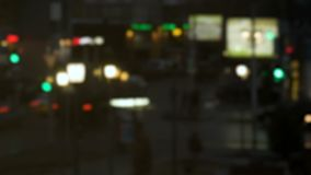 Crossroads in the city in the evening. Accelerated motion. Traffic lights, billboards, traffic and pedestrians. Bokeh, defocused. Lens. Time-lapse recording stock footage