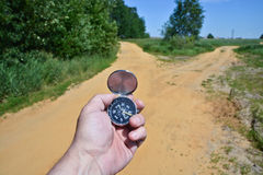 At the crossroads. Compass in the hand against the fork of the trail in the woods stock image