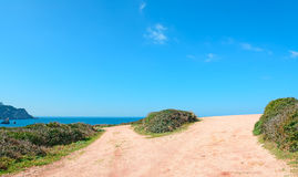 Crossroads by the sea. Crossroads in a red country road by Porticciolo shore, Sardinia Stock Photos