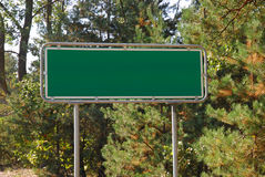 Crossroads signpost. Green background on the road Stock Photos