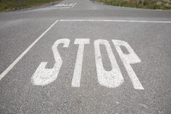 Crossroads with stop signal painted on asphalt Stock Photo