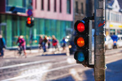 Crossroads with traffic lights in the city. Riga. Pedestrians and cyclists in colorful clothes at the crossroads with traffic lights in the city against the Royalty Free Stock Images