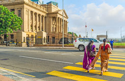 On the crosswalk. COLOMBO, SRI LANKA - DECEMBER 6, 2016: The women in traditional sari dresses walk across the street to the building of Presidential Secretariat Royalty Free Stock Image