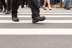 Crosswalk and anonymous people crossing the street. Royalty Free Stock Images
