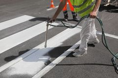 Crosswalk repairing and painting. Worker spraying pedestrian crosswalk at a street,  repairing and painting Royalty Free Stock Photo