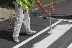 Crosswalk repairing and painting. Worker spraying pedestrian crosswalk at a street,  repairing and painting Stock Image