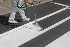 Crosswalk repairing and painting, worker using tool. One adult worker spraying pedestrian crosswalk at a street using spraygun Stock Images