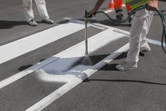 Crosswalk repairing and painting, worker using tool. One adult worker spraying pedestrian crosswalk at a street using spraygun Stock Photo