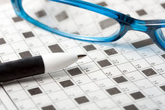 Crossword. Pencil spectacles on crossword puzzle background Stock Image