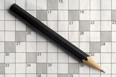 Crossword. An empty crossword puzzle with a black pencil on it Royalty Free Stock Photo