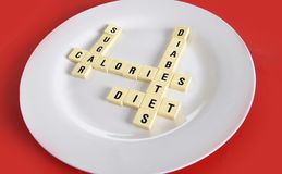 Crossword game on dish on table red mat with words sugar , calories, diabetes and diet taking in sugar abuse health risk Royalty Free Stock Photos