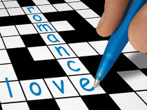 Crossword - love and romance. Hand with pen Royalty Free Stock Images