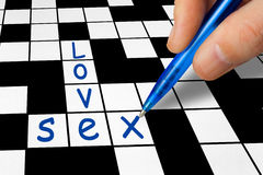 Crossword - Love and Sex. Hand filling in a crossword - Love and Sex Royalty Free Stock Photography