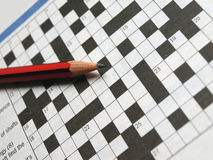 Crossword and Pencil. Closeup of red pencil on blank crossword Royalty Free Stock Photo