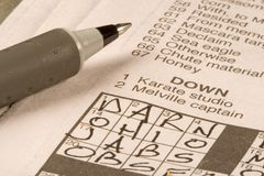 Crossword Puzzle. Newspaper crossword puzzle being solved by exercising the brain Royalty Free Stock Photos