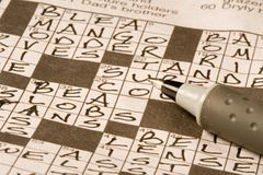 Crossword Puzzle. Newspaper crossword puzzle being solved by exercising the brain Stock Photo