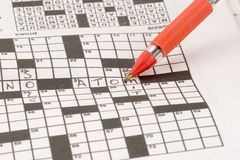Crossword Puzzle. Being solved with an orange ballpoint pen Stock Photography