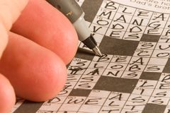 Crossword Puzzle. Newspaper crossword puzzle being solved by exercising the brain Royalty Free Stock Photography